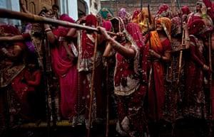 Lathmar Holi : Women wait with wooden sticks in Nandgaon