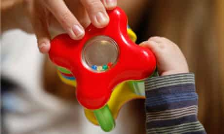 Baby's and mother's hands on toy