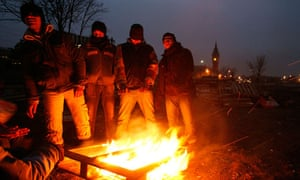 Asylum seekers warm themselves near the harbour and city hall of Calais