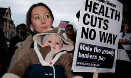 A woman protests in London against the health cuts.