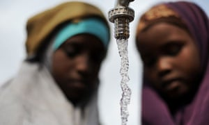 Two Somali girls watch water fill their jerry cans