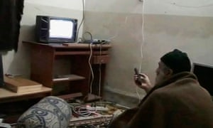 Osama bin Laden is shown watching himself on television