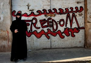 Inside northern Syria: A woman stands next to a graffiti that reads 'Freedom'
