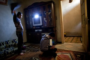 Inside northern Syria: Mohammed prays as Tareq prepares to leave their house, Kafar Taharim