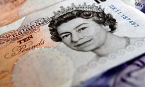 ten pound note on pile of cash