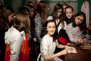 24 hours in pictures: Berlin, Germany: Students surround the wax figure of Anne Frank
