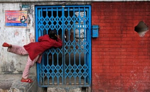 24 hours in pictures: Godawari, Nepal: A girl looks through a gate of a temple