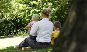 Back view of a mother sitting in the park with two young children