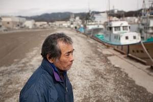 Japan tsunami: Wataru Sato, 63, stands by Kesennuma harbour as divers search