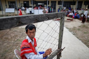 Burma elections: An official keeps the gates open for people arriving at a polling station