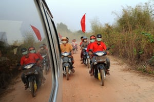 Burma elections: Supporters ride motorcycles next to Aung San Suu Kyi's car