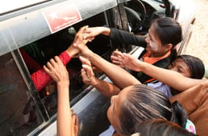 Burma elections: Supporters shake hands with Aung San Suu Kyi, sitting in her vehicle
