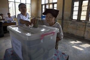 Burma elections count: A Burmese woman receives help putting her ballot in the box