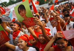 Burma elections count: Supporters of the NLD party cheer watching increasing votes on a screen