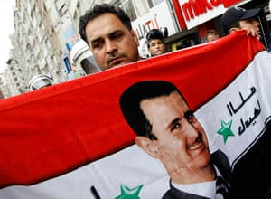 Syrian protests: A supporter waves a flag with the face of Syrian President Bashar al-Assad