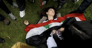 Syrian protests: A demonstrator lies on ground after Turkish riot police used tear gas