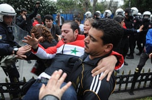 Syrian protests: A demonstrator is carried away after Turkish police release tear gas
