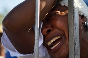 Haiti - A longer view: A woman cries as she prays during the Holy Week procession