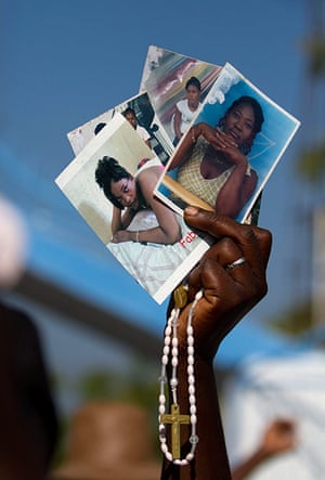 Haiti - A longer view: People bring pictures of their loved ones to the procession
