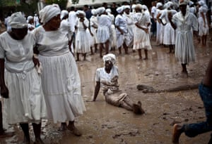 Haiti - A longer view: A Voodoo believer sits on the mud during the ceremony in Souvenance, Haiti