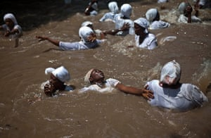 Haiti - A longer view: Believers swim in a sacred pool in Souvenance, Haiti