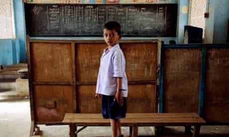 An Indian school boy stands on a class r