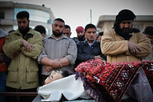 Aleppo, Syria: Men say prayers near the body of a man killed during clashes