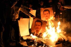 Aleppo, Syria: Young men burn posters of Bashr al-Assad during a night demonstration