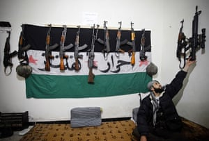 Aleppo, Syria: A rebel of the Free Syrian Army reaches for his weapon in a safehouse