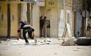 Aleppo, Syria: A rebel of the Free Syrian Army runs after placing an IED in the road