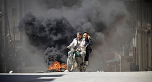 Aleppo, Syria: Citizens of Saraquib City flee the town on motorcycle while car tyres burn