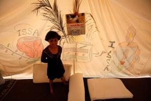 Boynuyogun refugee camp: A Syrian refugee stands beside a drawing on a tent at Boynuyogun camp