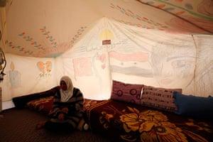 Boynuyogun refugee camp: A Syrian refugee sits beside a drawings on a tent canvas at Boynuyogun camp