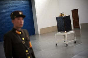 From the agencies: A soldier stands guard next to satellite