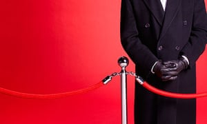 Doorman at red carpet event guarding rope barrier entrance