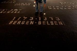 Holocaust memorial: A Holocaust survivor lays flowers next to the names of concentration camps