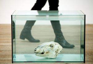 Damien Hirst: A woman walks past one of Hirst's sheep's head artworks
