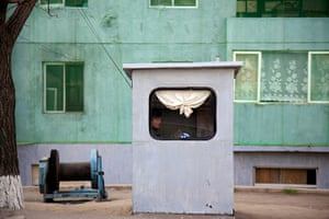 Longer view: A woman sits inside a booth on a street in Pyongyang, North Korea