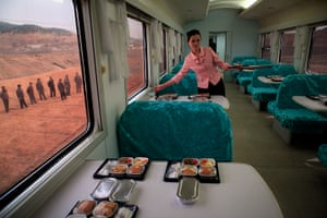 Longer view: A North Korean waitress serves packaged meals for lunch on a train