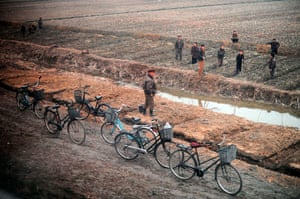 Longer view: North Koreans are seen from the window of a train working in a field