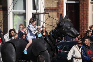 Liverpool Royal de Luxe: A girl rides the giant pet dog of the Little Girl Giant Marionette