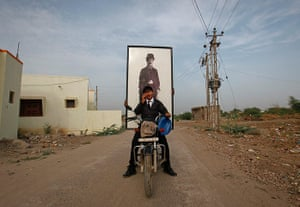 From the Agencies: A man drives a motorbike with a passenger holding a portrait of Chaplin
