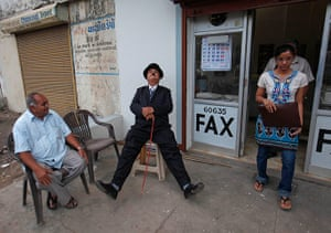 From the Agencies: Ashok Aswani dressed as Chaplin sits outside a shop in Adipur