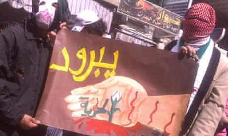 Demonstrators hold a sign during a protest against Syria's President Bashar al-Assad