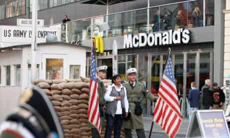 US 'soldiers' pose with tourists for pictures at Checkpoint Charlie