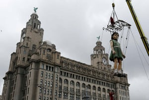Liverpool Puppets: A giant puppet of a girl is lifted into position outside the Liver Building