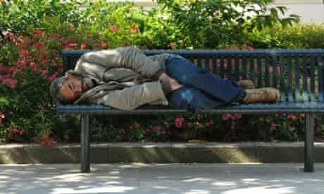 A vagrant sleeping on a public bench in the summer