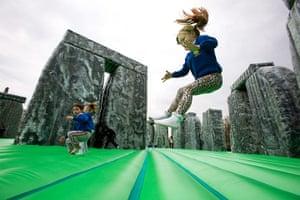 Glasgow Festival: A school girl bounces on Jeremy Deller's Stone Henge  bouncy castle