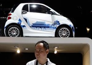 Beijing motor show: A man stands below a Mercedes-Benz Smart car on display