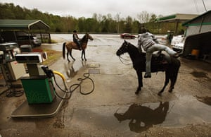 Booneville, Kentucky: Horse riders prepare to depart after a break at a gas station